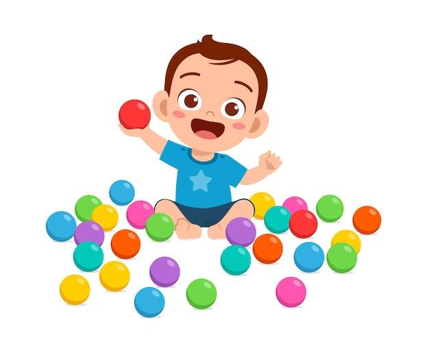 Mignon petit bébé jouant avec des boules colorées