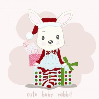 Mignon petit dessin animé lapin usure robe santa claus et boîte-cadeau. style dessiné à la main