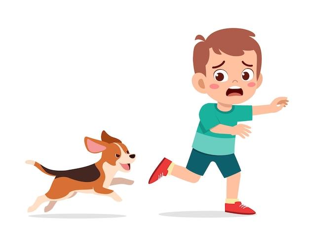 Mignon petit garçon effrayé car poursuivi par un mauvais chien