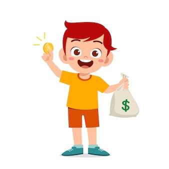 Mignon petit garçon enfant portant un sac d'argent et de pièces