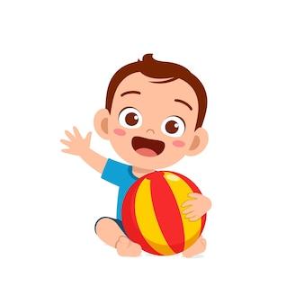 Mignon petit garçon jouant avec une grosse balle