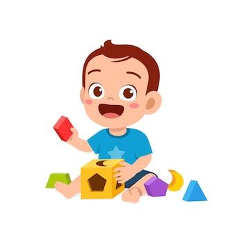 Mignon petit garçon jouant avec un puzzle coloré