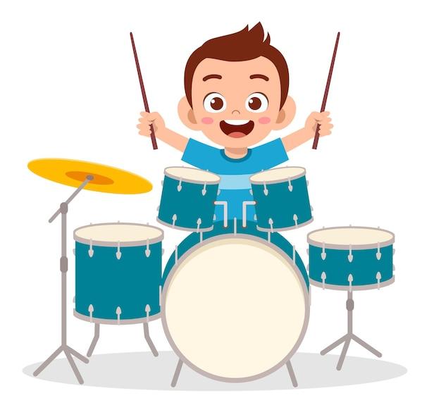 Mignon petit garçon joue du tambour en concert