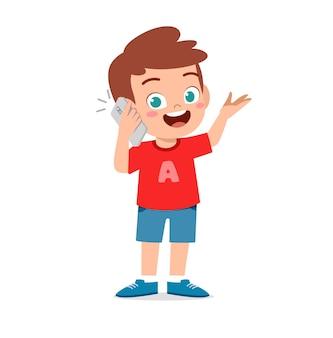 Mignon petit garçon parle à l'aide d'un téléphone mobile