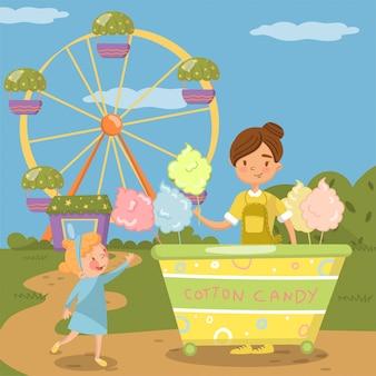 Mignonne petite fille bying barbe à papa du chariot de nourriture de rue devant la grande roue dans le parc d'attractions