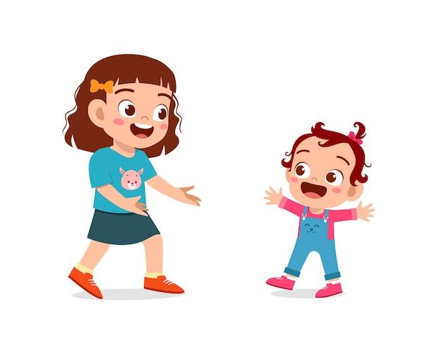 Mignonne petite fille joue avec bébé frère ensemble et apprend à marcher