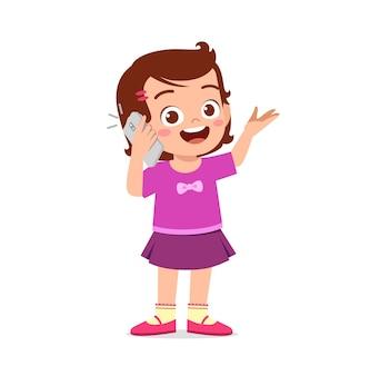 Mignonne petite fille parle à l'aide d'un téléphone mobile