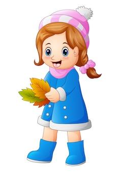 Mignonne petite fille tenant des feuilles d'automne