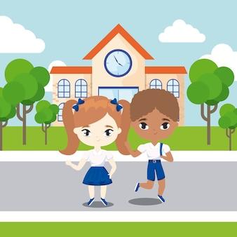 Mignons petits étudiants devant le bâtiment de l'école