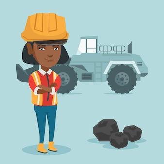 Mineur debout avec une excavatrice.