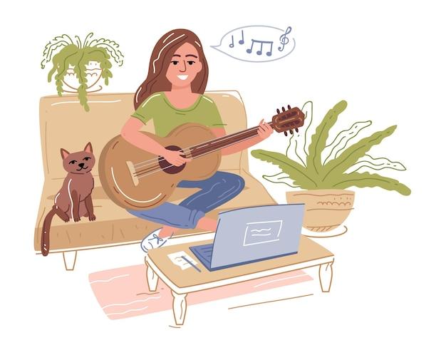 Mise au point sélective d'une jeune fille jouant de la guitare acoustique près d'un ordinateur portable