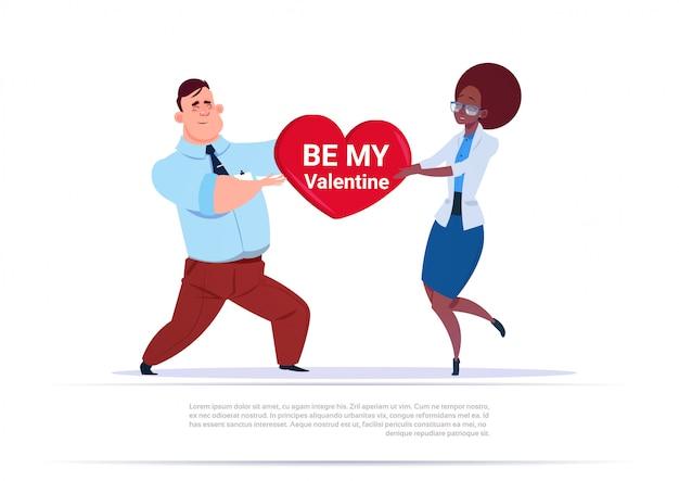 Mix race couple tenant en forme de cœur, soyez mon valentin salutation love day concept de vacances