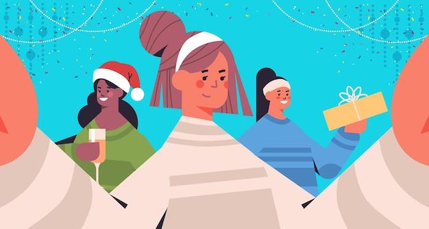 Mix race filles prenant selfie photo sur smartphone caméra femmes s'amusant nouvel an vacances de noël célébration concept illustration vectorielle portrait horizontal