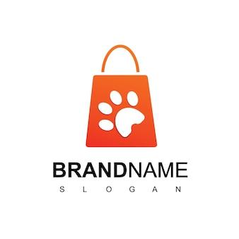 Modèle de conception de logo d'animalerie avec la patte de silhouette sur le symbole de sac à provisions