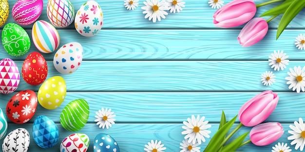 Modèle de joyeuses pâques avec des oeufs de pâques colorés et des fleurs sur une table en bois