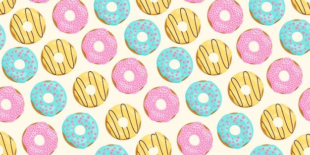 Modèle sans couture avec beignets de couleur glaçage bleu jaune rose