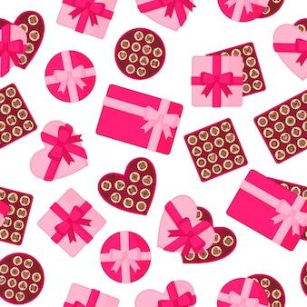 Modèle sans couture avec des boîtes roses de chocolats de différentes formes.