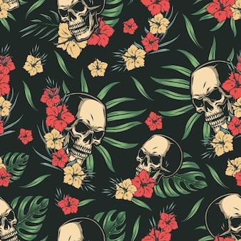 Modèle sans couture coloré tropical avec des crânes, des fleurs d'hibiscus, des feuilles de palmier et de monstera