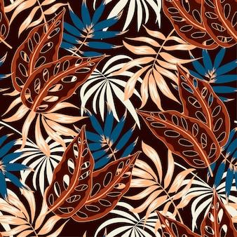 Modèle sans couture avec des feuilles tropicales brunes et bleues.