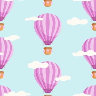 Modèle sans couture avec des montgolfières et des nuages sur fond bleu.