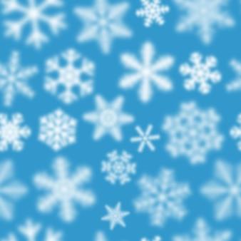Modèle sans couture de noël de flocons de neige défocalisés blancs sur fond bleu clair