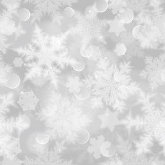 Modèle sans couture de noël avec des flocons de neige flous blancs, des reflets et des étincelles sur fond gris