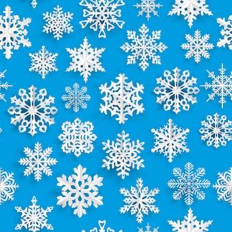 Modèle sans couture de noël avec des flocons de neige en papier blanc sur fond bleu clair