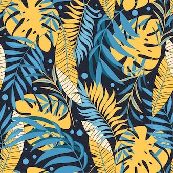 Modèle sans couture tropical original avec des feuilles et des plantes jaunes et bleues