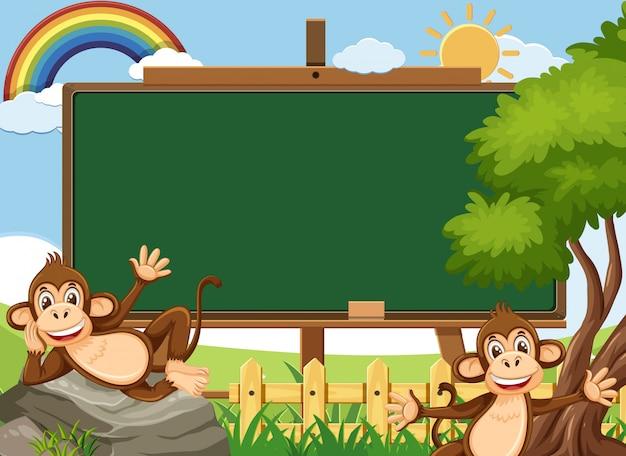 Modèle de tableau noir avec deux singes heureux dans le parc
