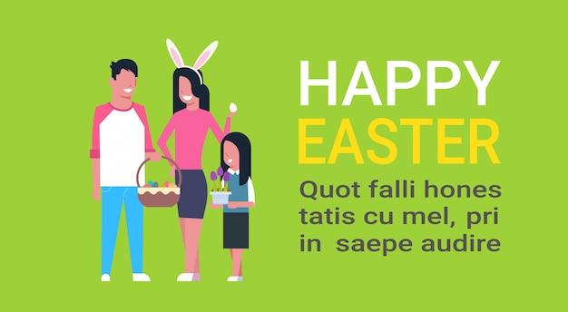 Modèle de texte joyeuses pâques avec jeune famille célébrant les vacances de printemps portent des oreilles de lapin et tenant un panier avec des oeufs