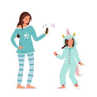 Moment maman et fille. un adulte et un enfant vêtus de jolis vêtements de nuit bleue dansent sur la musique. vacances en famille ou soirée pyjama