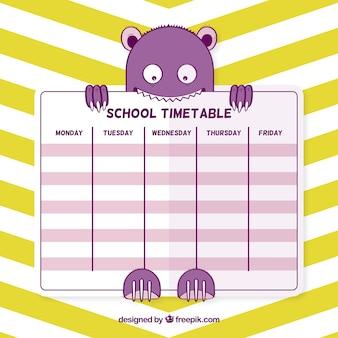 Monstre drôle avec le calendrier scolaire