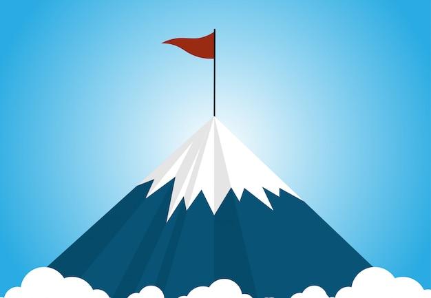 Une montagne enneigée au-dessus du niveau des nuages avec un drapeau rouge au sommet de la montagne sur ciel bleu