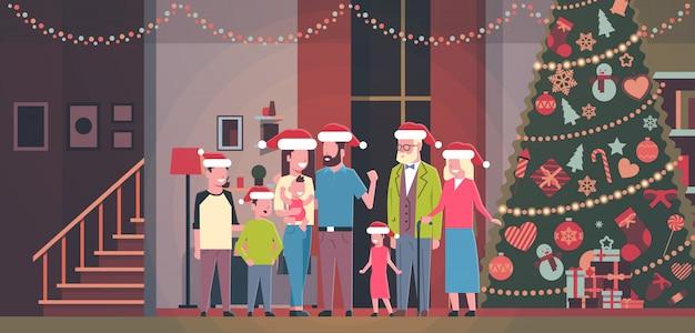 Multi génération famille debout dans maison près décoré sapin bonne année joyeux noël concept plat horizontal
