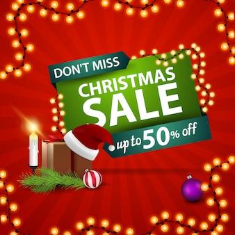 Ne manquez pas, vente de noël. bannière de réduction rouge et vert avec cadeau avec chapeau de père noël, bougies, branche d'arbre de noël et boule de noël