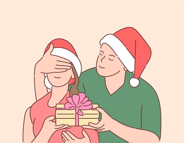 Noël, cadeau, concept de réveillon du nouvel an. un jeune homme heureux a préparé une surprise pour sa petite amie.