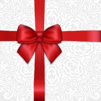 Noeud de ruban de satin rouge brillant vacances sur fond ornemental de dentelle blanche