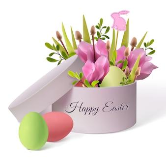 Oeufs de pâques joyeux avec des fleurs dans une boîte rose arrondie.