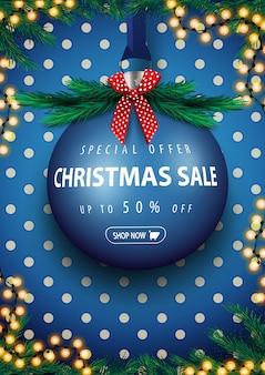 Offre spéciale, vente de noël, bannière de réduction verticale bleue avec grosse boule de noël bleue avec offre