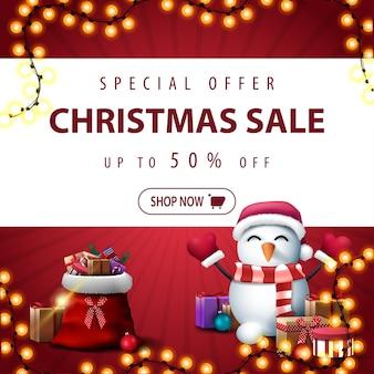 Offre spéciale, vente de noël, jusqu'à 50 rabais, bannière de réduction carrée rouge avec bande horizontale blanche, guirlande, sac du père noël avec des cadeaux et bonhomme de neige en chapeau de père noël avec des cadeaux