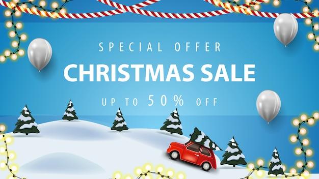 Offre spéciale, vente de noël, jusqu'à 50% de réduction, bannière de remise bleue avec ballons blancs, guirlandes et paysage hivernal de dessin animé avec une voiture vintage rouge portant un arbre de noël