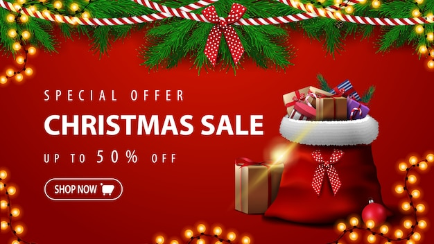 Offre spéciale, vente de noël, jusqu'à 50% de réduction, superbe bannière rouge avec des branches d'arbres de noël, des guirlandes et un sac du père noël avec des cadeaux