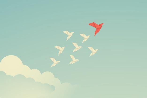 Oiseau en papier origami rouge menant parmi les blancs.