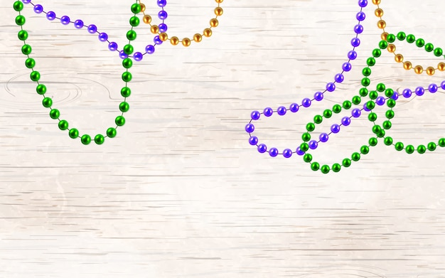 Or 3d multicolore, perles vertes, violettes isolées sur fond en bois. décorations de mardi gras.