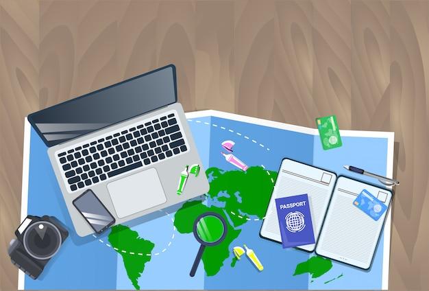 Ordinateur de bureau avec ordinateur portable, carte, appareil photo et concept de planification de vacances avec vue de dessus pour passeport
