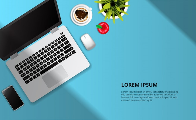 Ordinateur portable, pomme, tasse de café, plante vue de dessus sur le bureau bleu