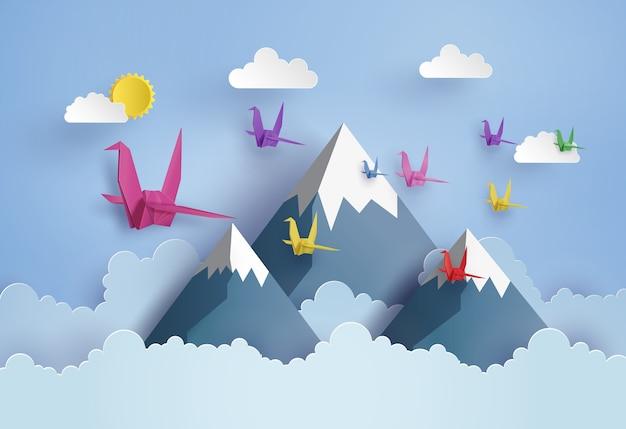Origami fait oiseau en papier coloré volant sur le ciel bleu