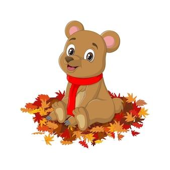 Ours de dessin animé mignon en écharpe rouge se trouve les feuilles d'automne