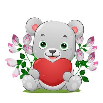 L'ours mignon est assis et tient le grand coeur sur sa main d'illustration