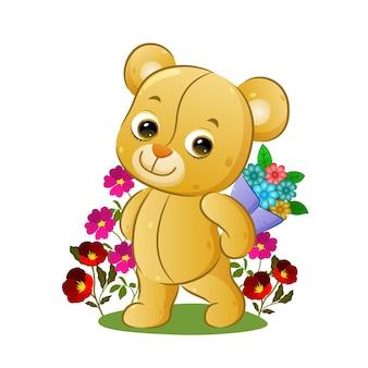 L'ours en peluche heureux tient un seau de fleurs derrière son dos dans le jardin de l'illustration
